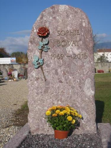 Monument funéraire en granit rouge avec rose et lettres en bronze